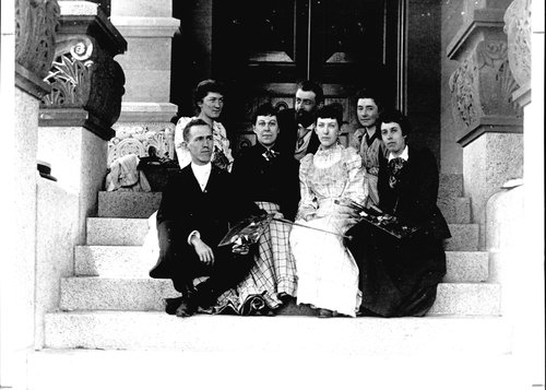 Seven Fine Arts students sitting on the Hall of Language steps.