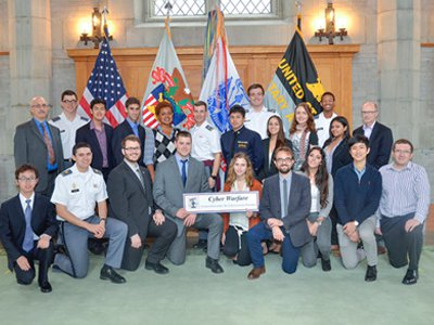 Hackett (center left, kneeling with sign) shown with his Cyberwarfare roundtable group.