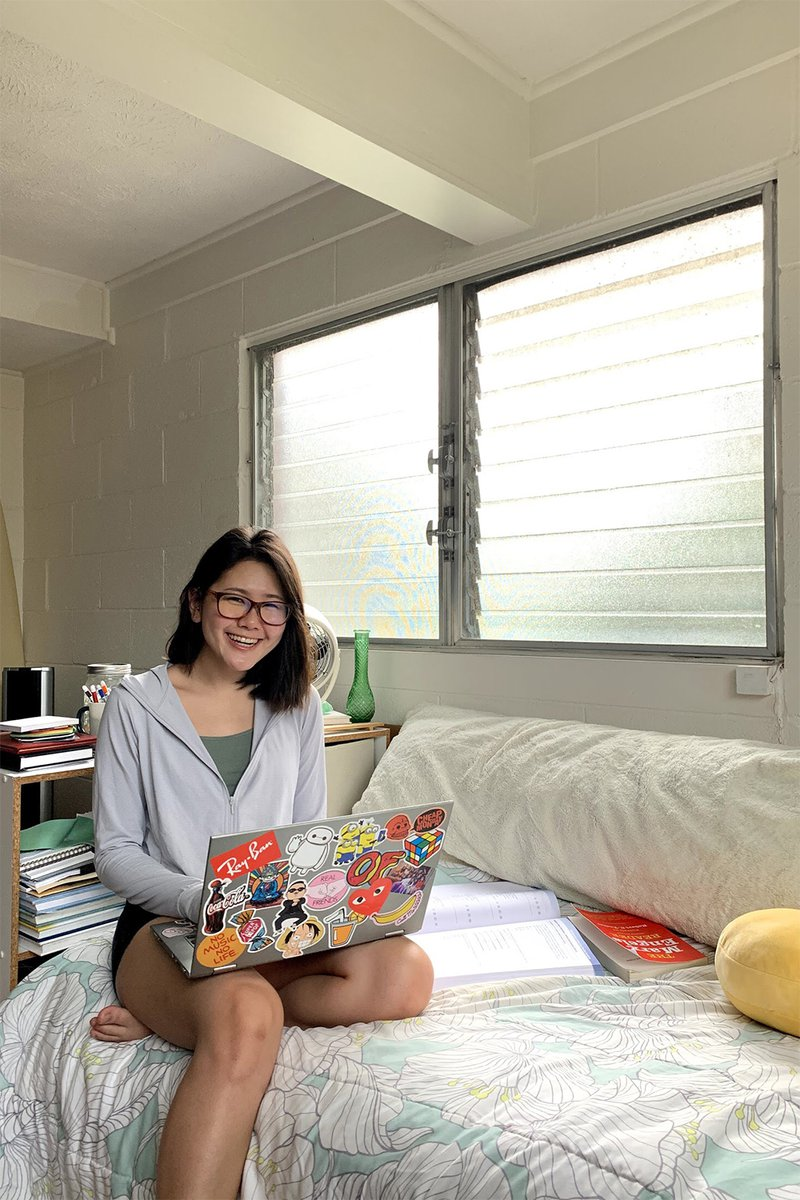 student on bed with laptop