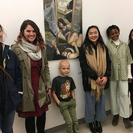 five adults and one child standing next to wall hung artwork