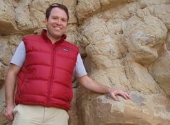Christopher Junium in Colorado, posing with 94 million-year-old rock
