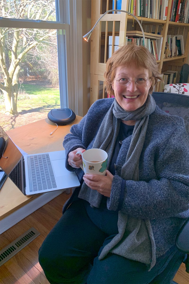dean karin ruhlandt in chair with cup of tea and laptop