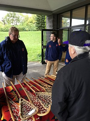 SU lacrosse coach John Desko examines handmade lacrosse sticks at the 2016 event