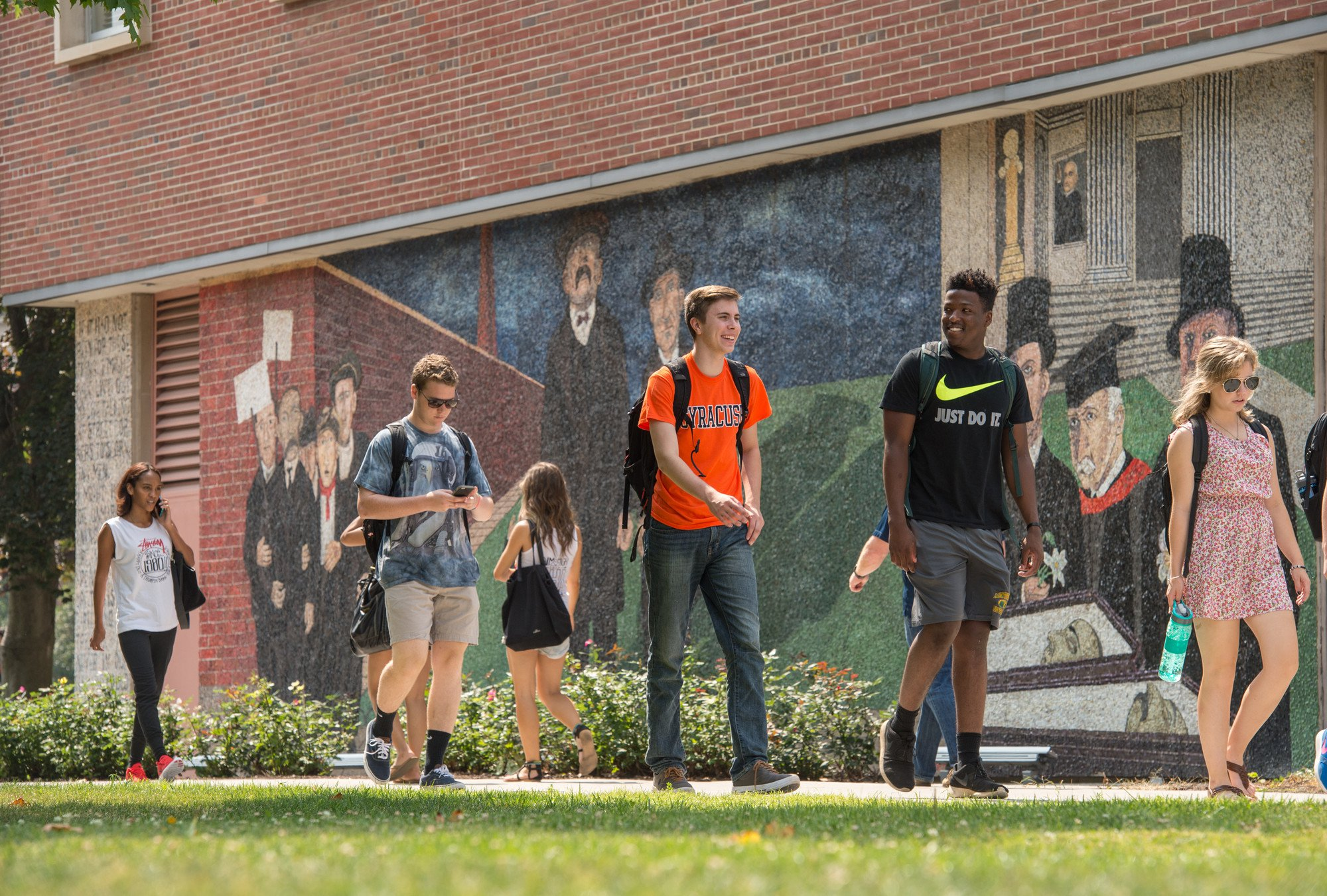 Students walk past a mural