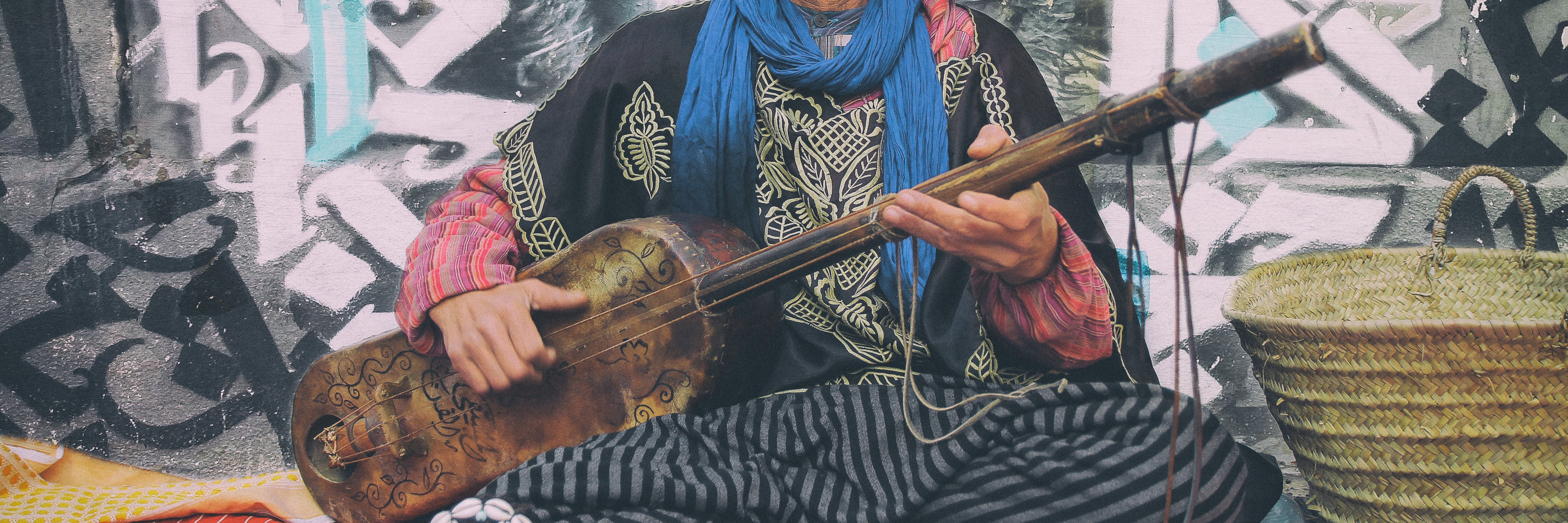 person playing a stringed musical instrument in Asilah, Morocco