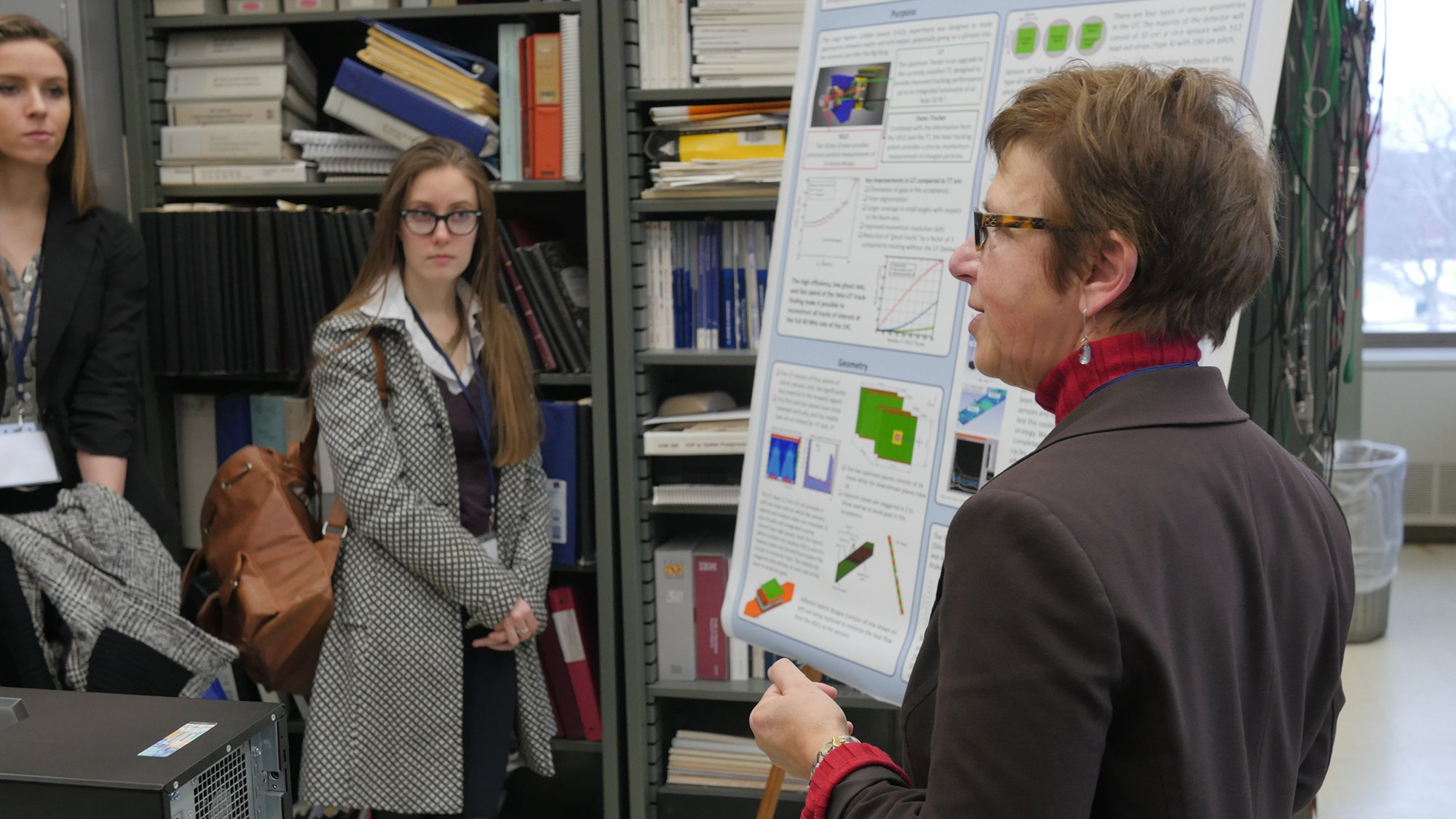 faculty member showing a research poster to two female students